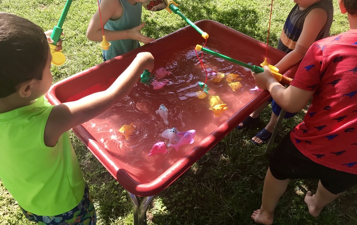 Students fishing in a a water tub.