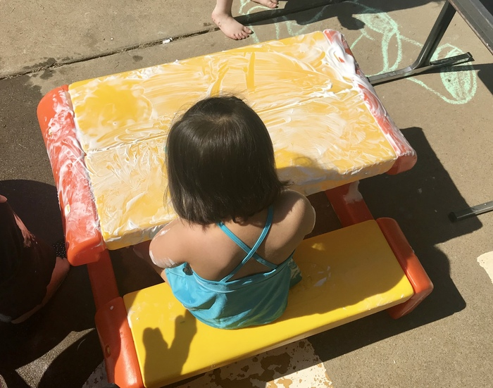 Student playing with foam on a play table.