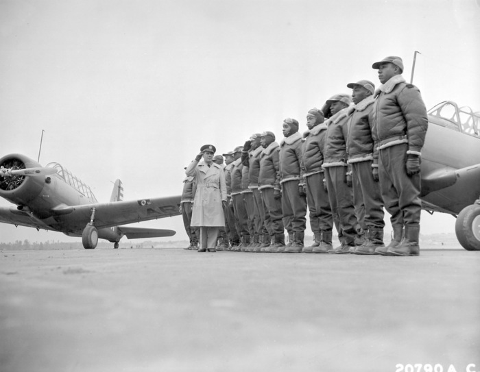 "Maj. James A. Ellison, commandant of the Tuskegee Army Flying School, returns the salute of Mac Ross, one of the first graduates, as he passes down the line during review of the first class. The term ""Tuskegee Airmen"" refers to all who were involved in the Army Air Corps program to train African Americans to fly and maintain combat aircraft. The Tuskegee Airmen included pilots, navigators, bombardiers, maintenance and support staff, instructors, and all the personnel who kept the planes in the air."