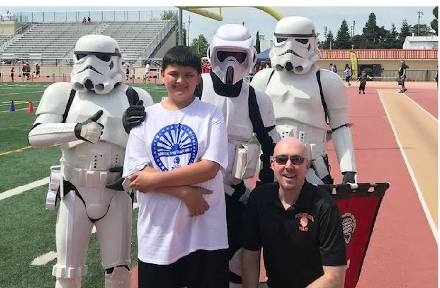 Image of student with Storm Troopers and Principal at Special Olympics